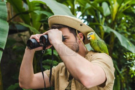 attractive young man with parrot on shoulder looking through binoculars in jungle
