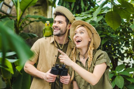 excited young couple in safari suits with parrot in rainforest