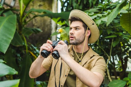 shocked young man with parrot on shoulder and binoculars in jungle
