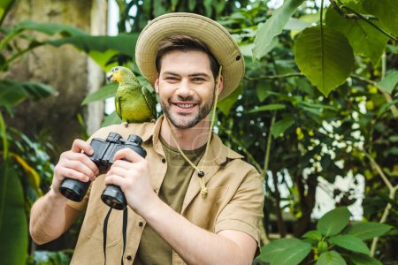 happy young man with parrot on shoulder and binoculars looking at camera