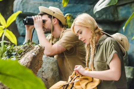 active young couple in safari suits with parrot hiking in jungle