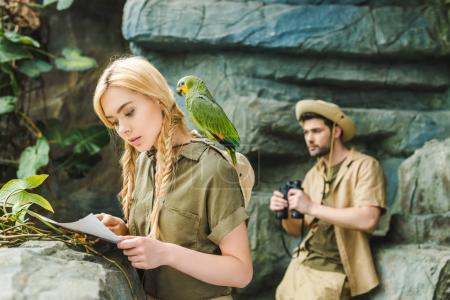 attractive young woman in safari suit with parrot and map navigating in jungle while her boyfriend looking through binoculars