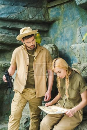 active young couple in safari suits trying to navigate in jungle