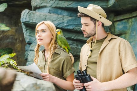 beautiful young couple in safari suits with parrot trying to navigate in jungle