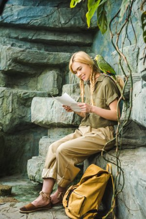 happy young woman in safari suit with parrot on shoulder and map sitting on rocks