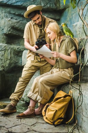 active young couple in safari suits with parrot hiking together