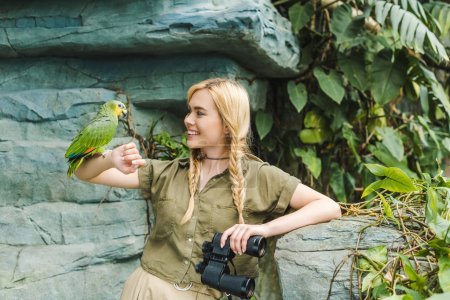attractive young woman in safari suit with parrot perching on arm in jungle
