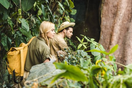 active young couple in safari suits hiking in jungle and looking somewhere impressed