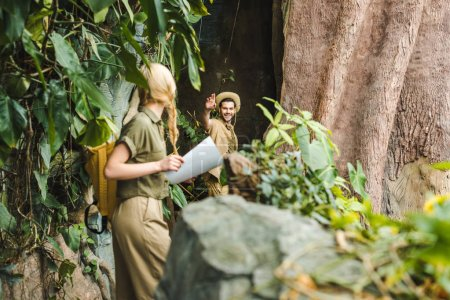 active young couple in safari suits hiking in jungle