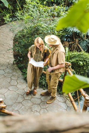 high angle view of beautiful young couple in safari suits with map in jungle