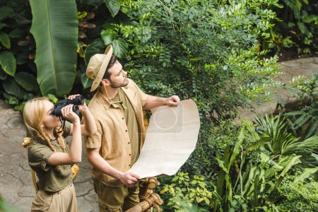 beautiful young couple in safari suits with map and binoculars in jungle