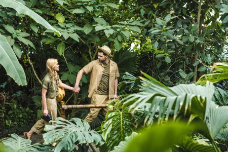 active young couple in safari suits holding hands and hiking in jungle
