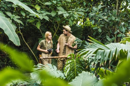 attractive young couple in safari suits holding hands and hiking in jungle