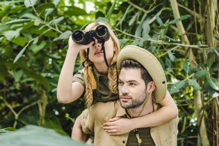 beautiful young couple in safari suits with binoculars hiking in jungle