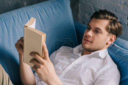 Photo pour Jeune homme se détendre à la maison sur le canapé avec livre - image libre de droit
