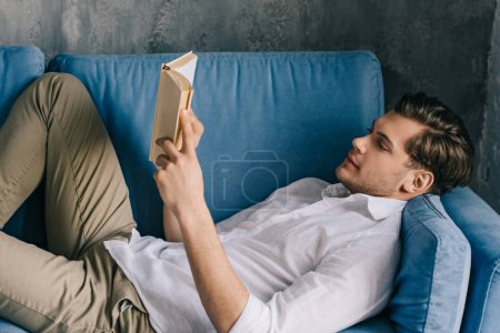 Photo pour Jeune homme lisant un livre allongé sur un canapé - image libre de droit