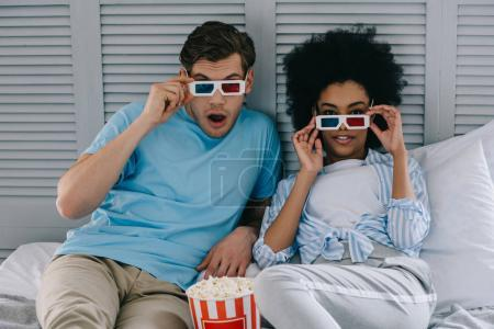 Multiracial boyfriend and girlfriend in stereoscopic glasses watching movie at home with popcorn