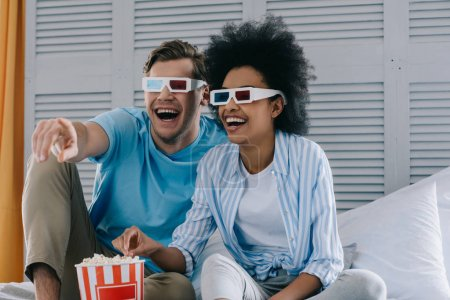 Laughing couple in anaglyph glasses watching movie at home with popcorn
