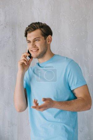 Photo pour Jeune homme, parler au téléphone de mur gris - image libre de droit