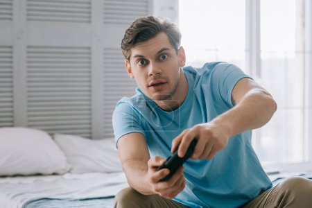 Photo for Surprised young man with joystick playing video game while sitting on bed - Royalty Free Image