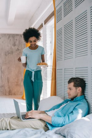 African american girl standing with breakfast by her boyfriend in bed with laptop