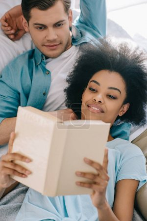 Relaxed couple reading book while lying in bed