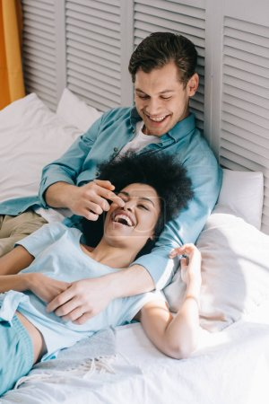Loving multiracial couple having fun on bed at home