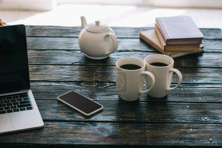 Tazas y tetera sobre mesa de madera con portátil y smartphone
