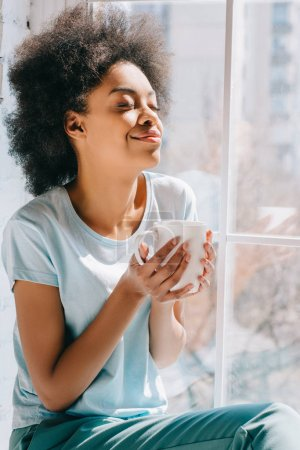 Relaxed african american girl holding cup of coffee while sitting on windowsill