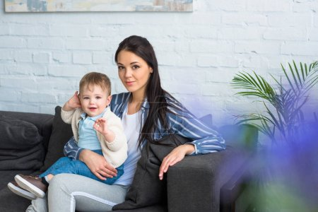 mother with adorable baby boy on hands sitting on sofa at home