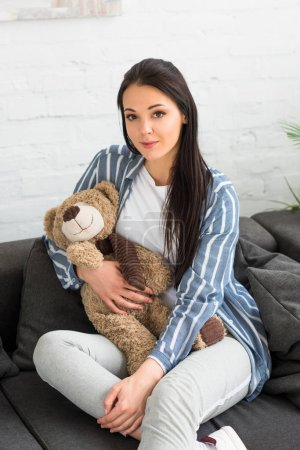 portrait of smiling woman with teddy bear resting on sofa at home