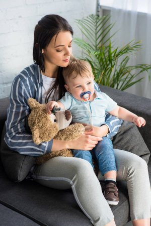young mother and little baby with pacifier and teddy bear sitting on sofa at home