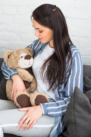 Photo pour Femme souriante avec ours en peluche au repos sur le canapé à la maison - image libre de droit