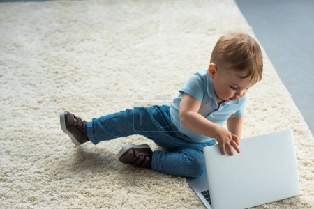 little baby boy with laptop sitting on floor at home