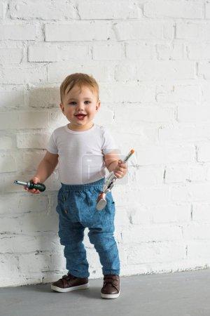 Foto de Feliz niño de bebé con los juguetes en pared de ladrillo blanco - Imagen libre de derechos