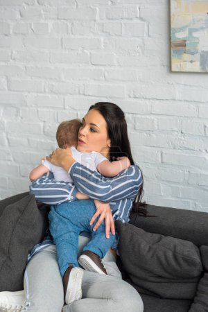 mother with little baby in hands resting on sofa at home