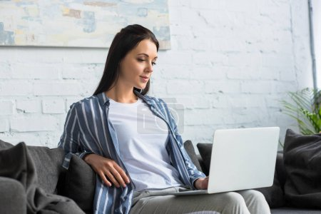 young focused woman using laptop on sofa at home