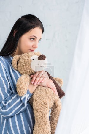 side view of pensive woman with teddy bear in hands looking away at home