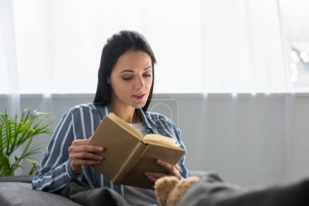 portrait of young woman reading book on sofa at home