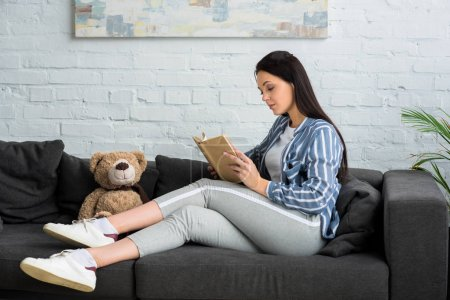 Photo pour Vue latérale de la jeune femme lisant livre sur canapé avec ours en peluche à la maison - image libre de droit