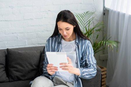 Photo pour Portrait de jeune femme à l'aide de tablette numérique sur canapé à la maison - image libre de droit