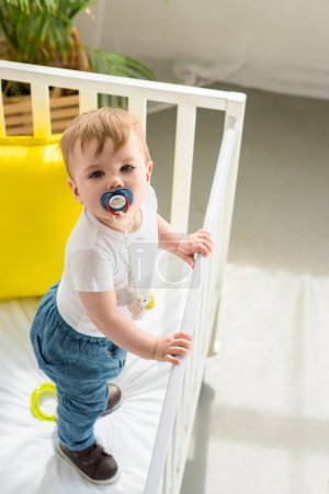 Photo for High angle view of cute little baby boy with pacifier in baby crib looking at camera at home - Royalty Free Image