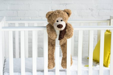 Photo for Close up view of teddy bear hanging on white wooden baby crib in room - Royalty Free Image