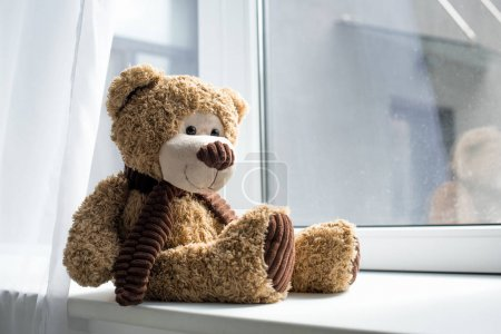 close up view of cute teddy bear on window sill