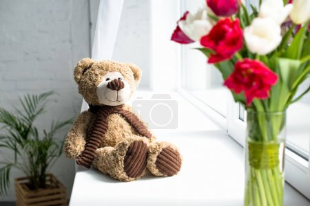 selective focus of teddy bear and bouquet of tulips in vase o window sill at home