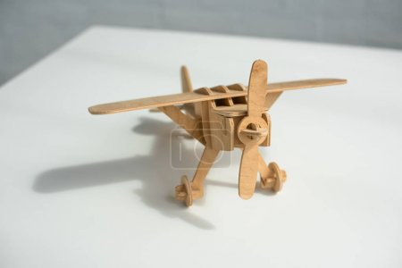 close up view of wooden toy plane on white tabletop