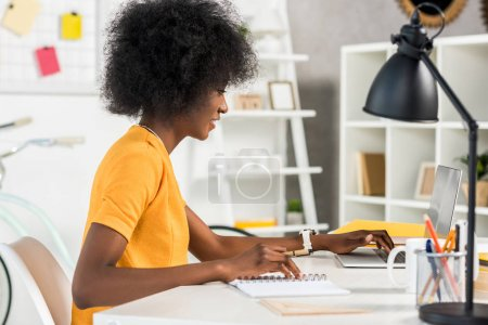 Photo for Side view of african american freelancer working on laptop at workplace at home - Royalty Free Image