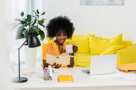 smiling african american woman with cup of coffee reading book at workplace with laptop at home