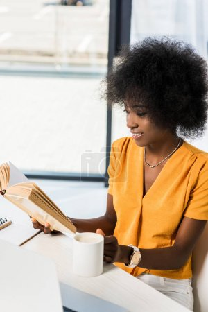 smiling african american with cup of coffee reading book at table at home office