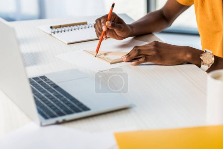 cropped shot of african american woman drawing at workplace with laptop at home